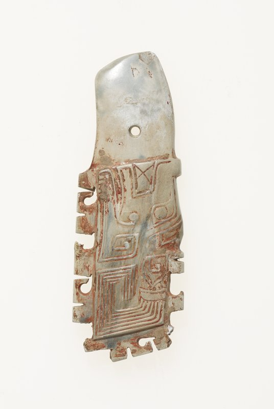 Jade handle with monster-mask design; incised on both sides identically; interrupted carved outline; the perforation is drilled from both sides. Ivory calcified jade with blue striation. Traces of red pigment and clay.