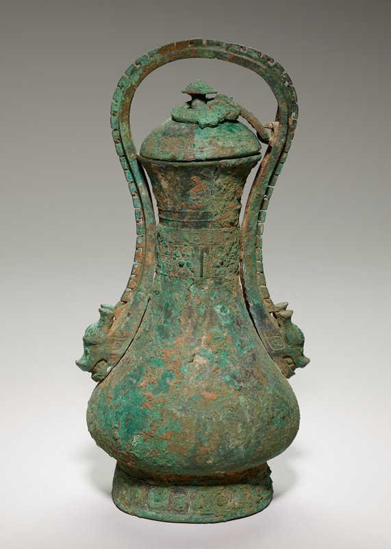 The graceful shape of a Hu flask is accentuated by the bold and forceful handle terminating in heavy animal masks with bottle horns. Springing from the space between the horns is a thick flange, deeply scored, that out-lines the sweep of the handle up and over the body of the vessel. The handle is attached to the domed and collarless lid by a curled-up gaping dragon, with a double row of scales, whose body encircles the conocal knob of the lid. The vessel is sparingly decorated with hands of pointed spirals on the lid, neck, and foot. Beneath the spirals on the neck belt is a band of dragonized t'ao-t'ieh in low relief. Patina blue-green with marks of mat wrapping.