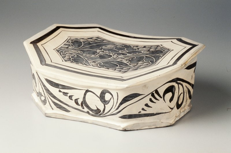 black and off-white; octagonal shape; slightly concaved top decorated with leafy floral stem; stylized floral band on sides