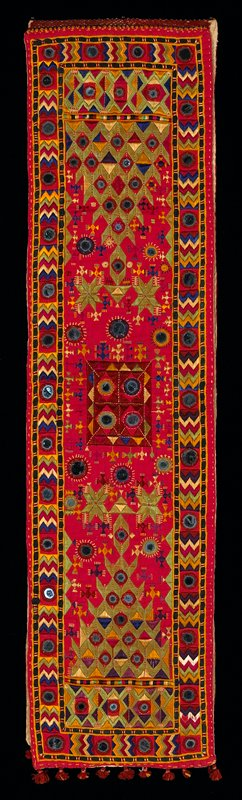 cotton ground in red is heavily embroidered in silk in green, purple, natural, navy, yellow, yellow/gold; mirrors (mica) are in several sizes; two rectangles needle stitched together; edges have silk tassels; back with natural colored cotton