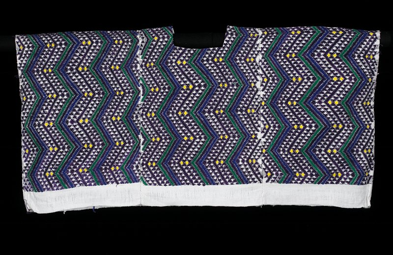 three white paneled huipil woven on a back strap loom; brocaded with vertical zigzag brocaded lightning designs (blue, purple and green stripes); yellow dots spread on the purple background represent human eyes in the darkness