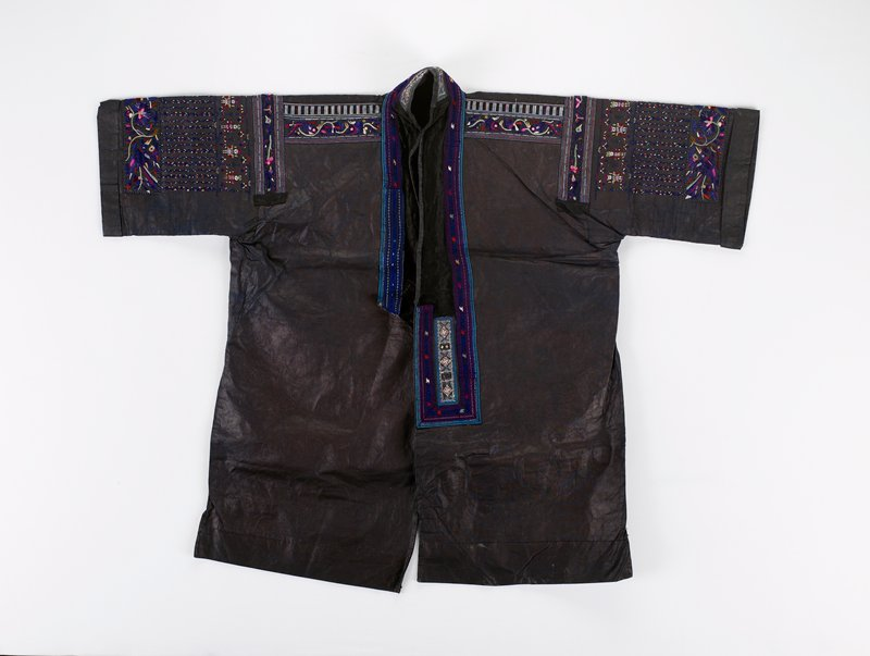 large jacket with short sleeves; black pounded indigo with purple, white and pink trim; embroidery of human forms, birds and flowers in bands down front, across shoulders and on sleeves; black velvet surrounds neck opening with stand up collar; some applique and metal disks front and back; lined with black pounded indigo; cuffs; front longer than back