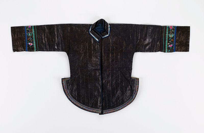 pounded jacket--very stiff--with fan bottom; narrow embroidery on bottom; open front with stand up collar; one snap at bottom; cuffs have bands of black silk embroidered with flora and fauna; blue lining
