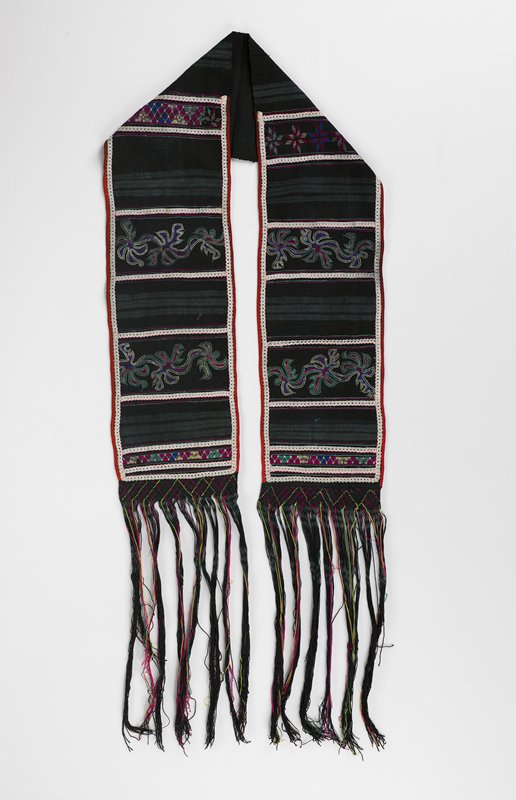 black with long fringe; embroidered in separated bands of chain, cross and satin stitch in white, pink, teal and blue; black ground fabric handwoven cotton; applied, handwoven band with long fringe; red cotton binding