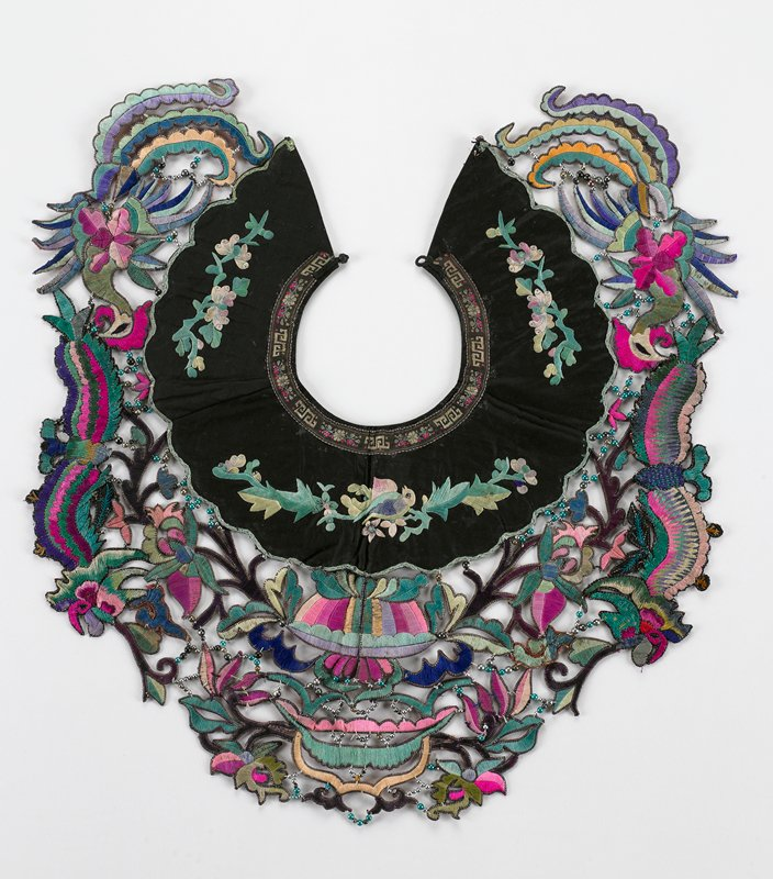 black, pink, green; edged with flat metallic strips; embroidered cutouts of flowers and petals joined together with thread; white teal and green beads; cutouts hang from scalloped, embroidered black yoke; finished with glued braid at neck edge; knot button and loop at back; collar forms circle when fastened