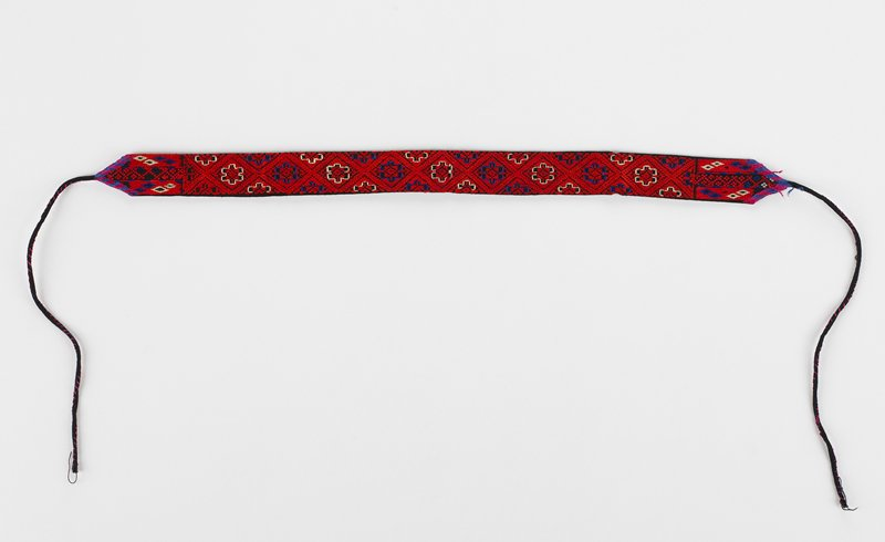 band with ties at each end has 9 embroidered diamond designs which include other geometric patterns; red, blue and white on black; black lining; may be a pair with 2004.67.469