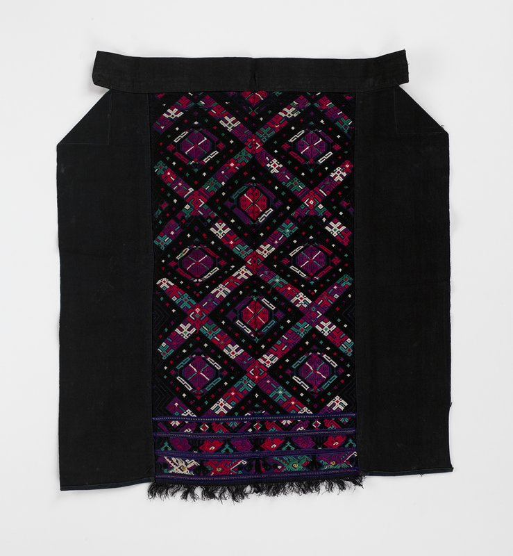 dark blue with center embroidered pattern of diagonal squares and geometrics in red, teal, black, purple and white; three embroidered bands with abstract patterns and fringe on bottom; side panels and waistband are black; no lining on embroidered section