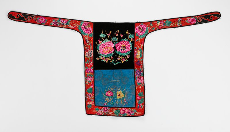 top half of black velvet; bottom of blue damask; red silk border; large floral machine embroidery with varigated thread in pink, green, yellow; unlined but bottom half and back of border are stiffened; narrow black band around each section including ties
