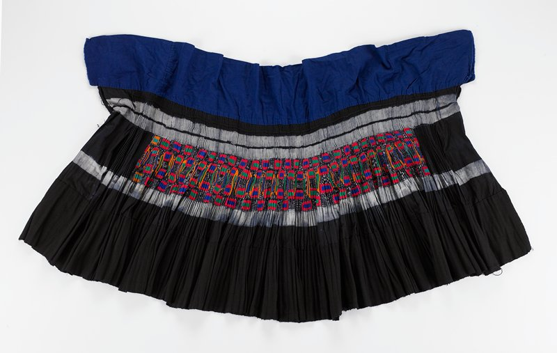 "large; dark; wrap style; accordian pleated; 6-1/2"" blue waistband; lower 7"" of doubled, coarse cotton; center section of batik, geometric pattern and colorful, appliqued pattern in gold, green, red and blue; no ties"