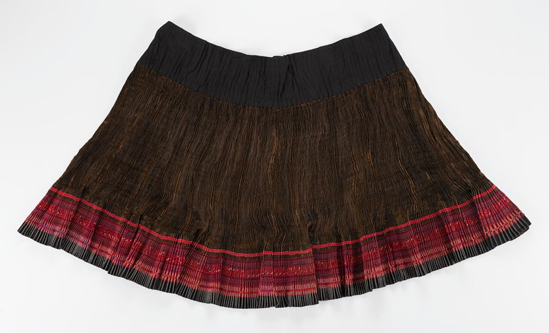 "tight accordian pleated skirt with wide (5-1/2"") black waistband with loops and ties; brown damask body with 5-3/4"" applied embroidery, lower border; border has five sections of alternating embroidery and ribbon tape in dark colors of red, black and white"