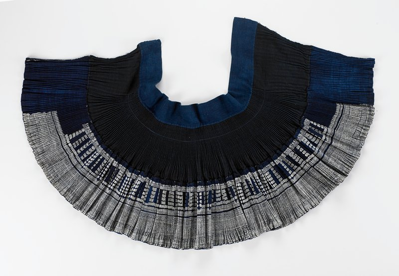 "coarse cotton wrap skirt; navy and white accordian pleated; reversable (?); blue 3"" wide waistband; added lower half has elaborate batik geometric pattern; no ties"