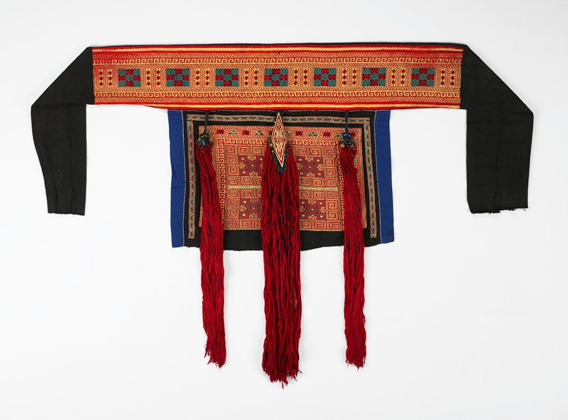 "pounded indigo with blue lining; geometric embroidered panel in red, yellow and green; top band heavily embroidered geometric design in red, yellow and green; 18"" black extensions on top band; three dimensional embroidered center attachment with two sets of silk tassels and beads; two side attachments of braided cotton yarn and beads"
