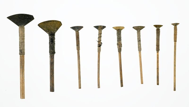 triangular metal blade with one pointed corner and one blunt corner; bamboo handle wrapped with string and attached to blade