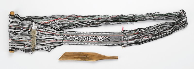 toe loom with weaving in progress; black and white geometric pattern with a red and a green stripe on either side of center pattern; red wooden sticks at end of work in progress; wooden dowel and wooden paddle