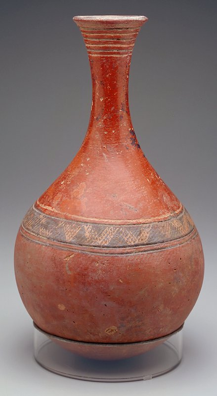 Round body with rounded bottom; tapering to a narrow, long neck which flares out at the mouth; red body with six incised lines around mouth and two incised lines around shoulder flanking a zigzagged band in brown and tan