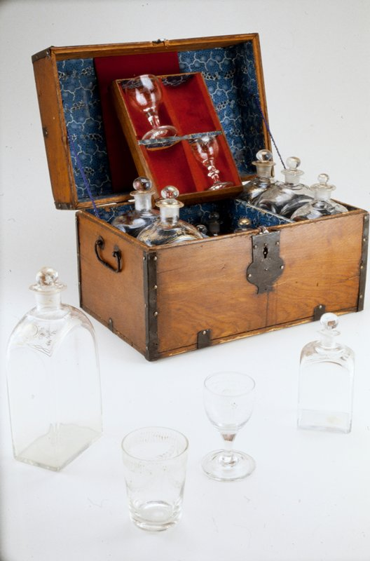 liquor chest,1780-1800, oak bound with iron fittings; lined in paper of black and white design on blue ground; containing six large and six small square decanters with stoppers, each in a compartment; also two wine glasses, one tumbler, one cordial glass in a removable tray; colorless, non-lead glass gilded in foliage designs along shoulders of decanters, stoppers and upper half of glasses; see cat. card for ind. msmsts