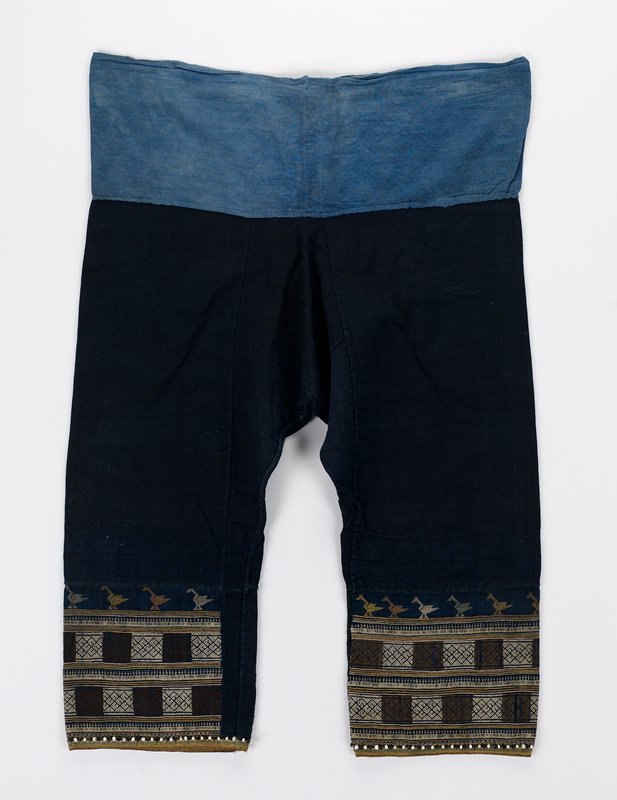medium blue waistband, dark blue legs; embroidered panels at bottom of each leg in brown, yellow, green and white, embellished with black and white beads; geometric motifs and birds