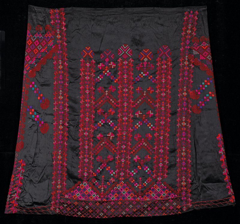 "black shiny synthetic satin; long vertical embroidered patterns in front--patterns said to be ""Tree of Life""; red and multicolor; plain black strip in back; embroidery along hem"