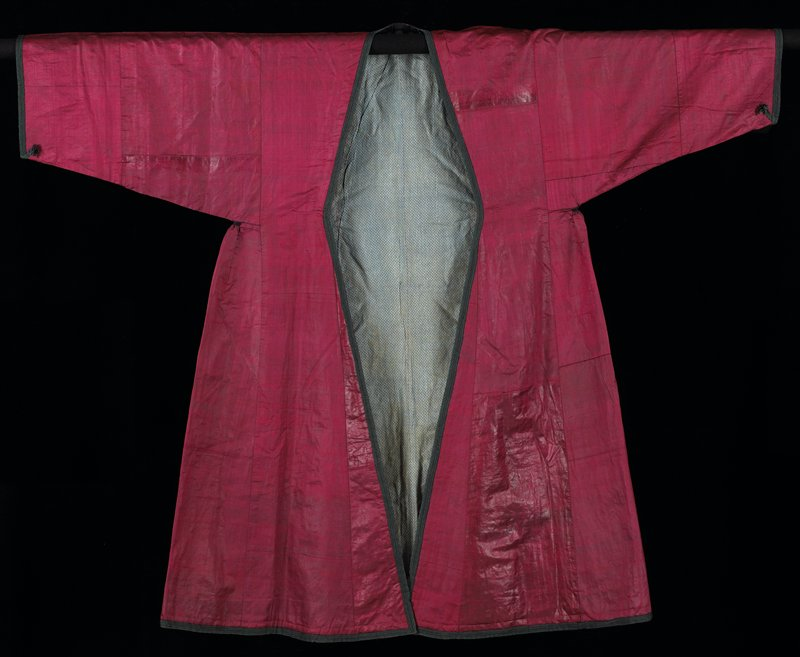large, shiny, wine colored, trimmed with green and black braid; waist tucks underarm; blue small print lining; silk ikat facings neck, front and hem