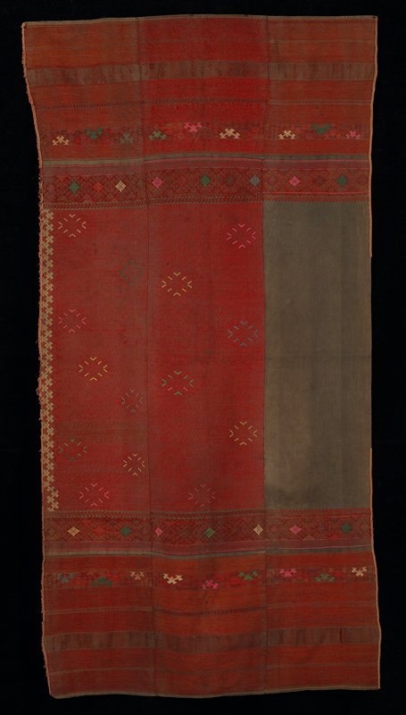 tightly woven; three sections, two primarily red with vertical strips of embroidery; third section has large solid grey piece in center