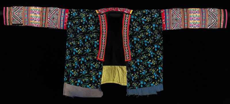 lined tunic body is color print on black corduroy; applique and embroidered bands on sleeve, separated by machine tape; longer fronts with applied embroidered bands on edges; rectangular back collar with applique and cross stitch
