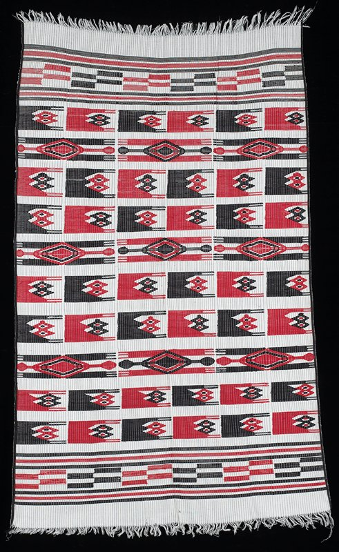 white background with thin black lines; red and black weft patterning figures; horizontal stripes at each end, alternating broken lines
