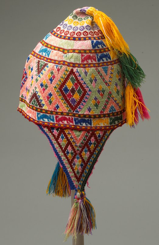 unlined; knitted hat with side flaps; horizontal geometric and animal pattern in multicolors; five tassels in pink, green, yellow and purple; tassels on flap sides are multicolored