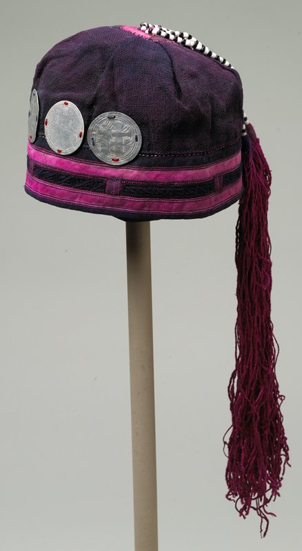 dark purple skull cap with horizontal pink bands and black embroidered band; three large silver disks with Asian pictograph embossing; five magenta silk tassels with black and white glass beads attached at center top