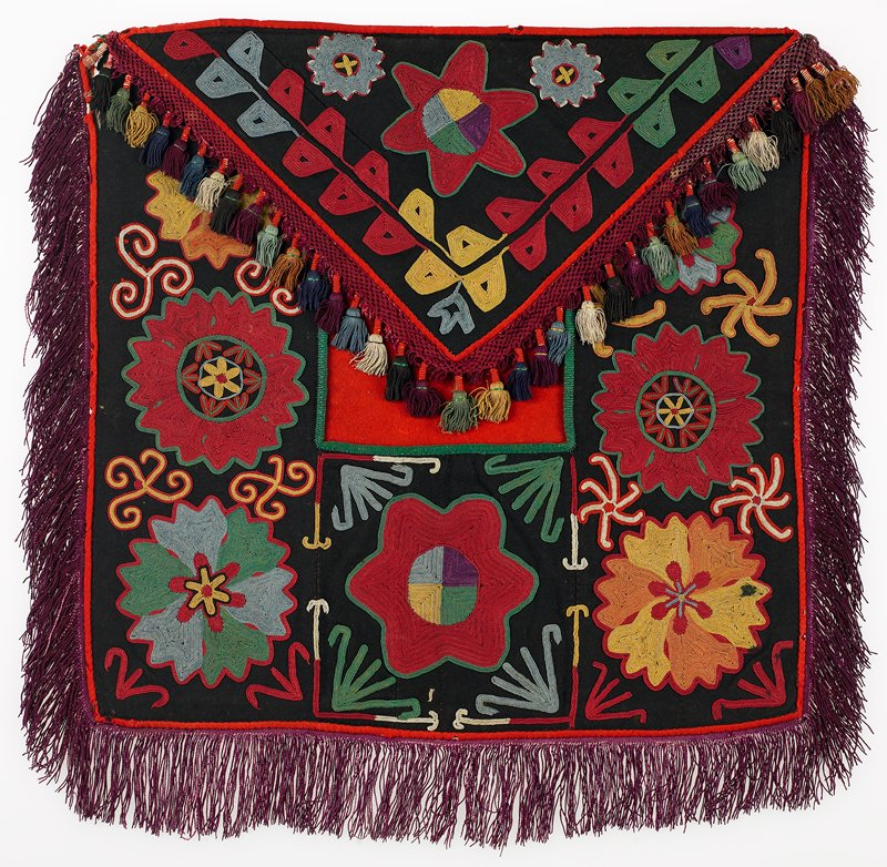 Braided-net fringe, fringe with warp-twined (tablet) heading, warp-twined (LM) edge, cloth band, Pieced ikat and printed lining. Black wool ground with polychrome silk embroidery, red wool edge binding, braided silk fringe with wrapped tassels. The red wool panel at the center is pieced with silk/cotton ikat under the flap. The panel is backed with printed cotton fabric, same as flap backing. Chain stitch