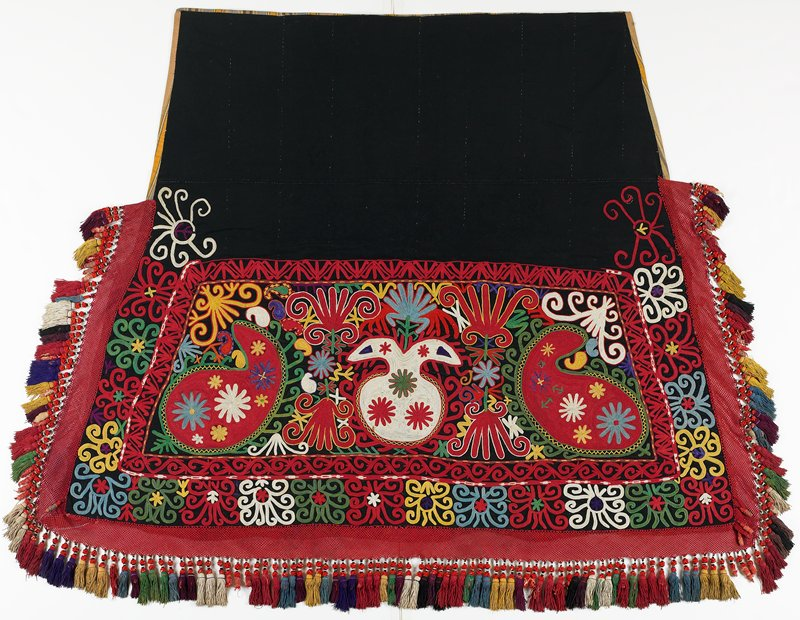 Braided-net fringe, Pieced, striped lining. Black wool ground with polychrome silk embroidery. There is a wide woven silk edging with silk and cotton tassels. The backing is woven striped cotton. Two tassels near bottom corners are inset bound above woven edge. Lower left corner has 2 tassels underneath.