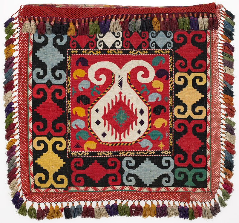 """Braided-net fringes, ikat band. Bag back: pieced, printed stripes and woven lining Overall cross stitch embroidery in silk and synthetic threads on a printed cotton ground. Crocheted fringe of cotton in two shades of red, with cotton tassels. there is an unembellished red cotton band at the top, which is covered by the fringe. The top opening of the bag is bound in silk/cotton ikat. The back of the bag is composed of two layers of printed cotton fabric. One intact hanging cord is present at the PR. a square 12.25"""" at center with white motif on red background with green, yellow, black, blue elements. Outer border: on black background multi-colored motifs."""