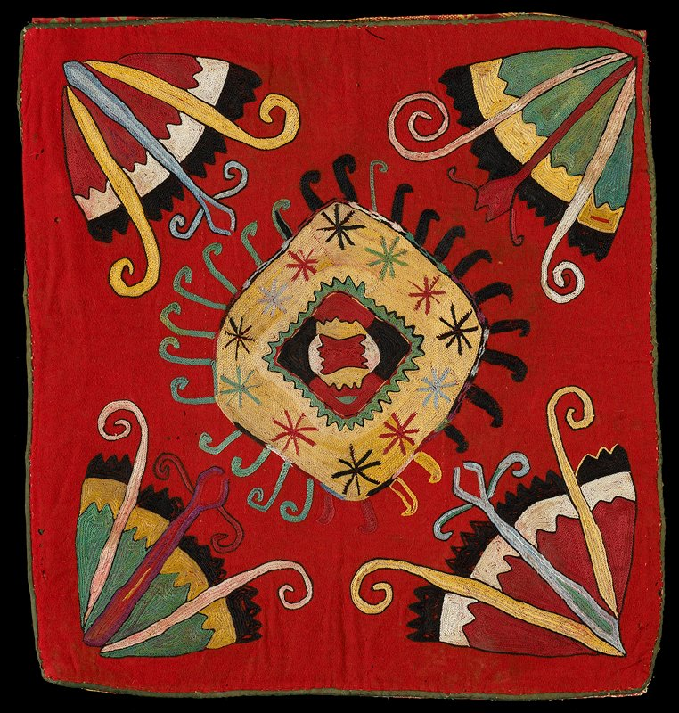 Cloth band, Pieced, printed lining. Red wool round with polychrome silk embroidery, cotton edge binding and printed cotton backing. Square center design and four corner images. Pieced, red print lining. Chain stitch dominates.