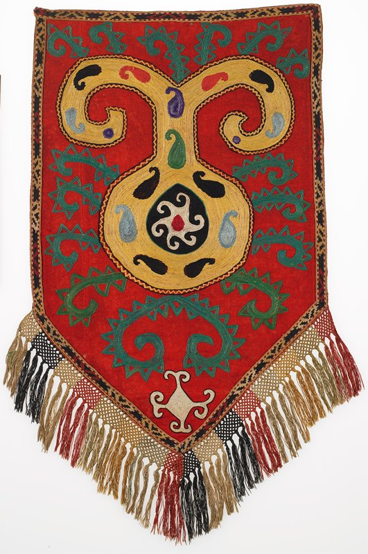 Braided-net fringe, embroidered band, Lined. Red wool ground with polychrome silk embroidery. The applied border on all sides is overall cross stitch embroidery in silk on a cotton ground. The backing is red cotton fabric. Part of a hanging loop is present on the PR corner.