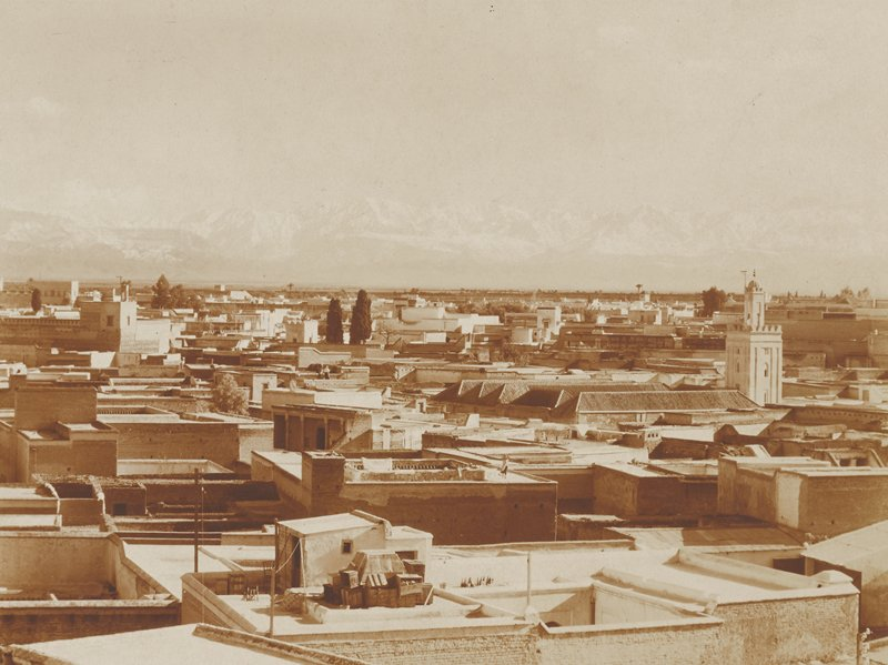view overlooking varied flat rooftops; square tower at R; hazy mountains far in background; Morocco