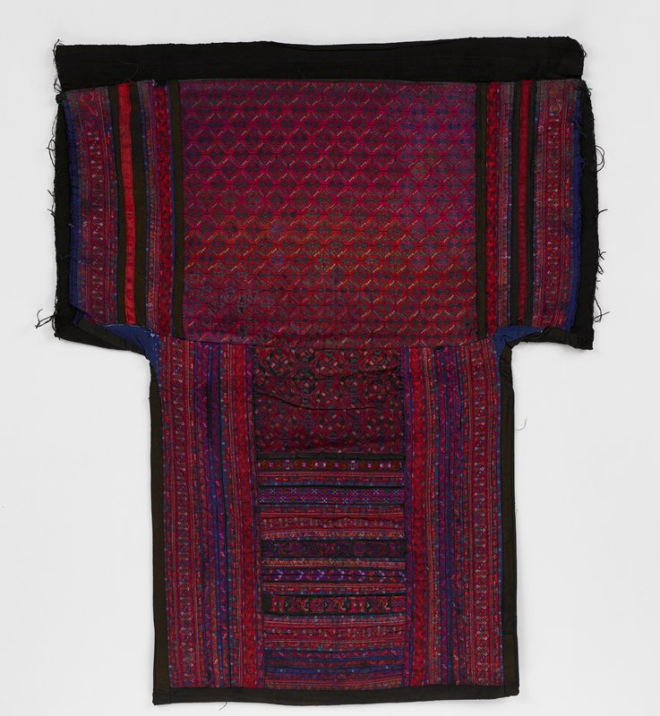 black lining; lower center panel has woven geometric pattern--deep red with multicolors; vertical borders with applied woven bands and tapes; upper panel center with horizontal applied embroidered bands and tapes and same on vertical edges