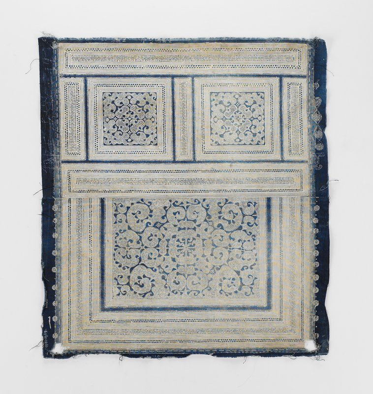 small scale batik--blue on off-white; two seamed pieces; lower panel--large rectangular swirling pattern surrounded on three sides by multi-linear border; upper panel--two squares of swirling pattern surrounded by linear bands
