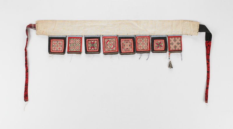 """love apron, Kueichow province; white belt with red ties; attached are eight cross stitched 2-3/4"""" x 3-1/2"""" squares in red, black and white; all beads missing except one on far right, 3"""" long including tassel"""