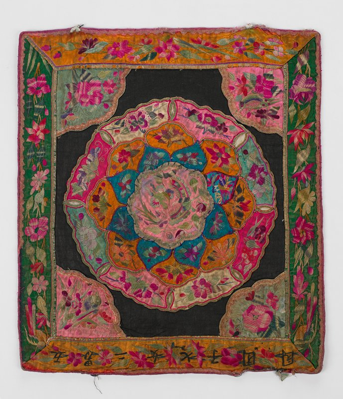 black cotton (linen?) square has three elaborate rows of floral embroidered petals forming large flower in pinks, aquas, orange and white with pink center; triangle corners in green and pink and borders in green and orange are embroidered in flowers and, at bottom, Chinese characters; pink trim on borders; black lining