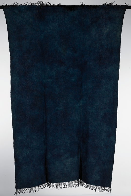 three panels hand stitched together; indigo dyed; blue mottled; warp fringe twisted and knotted at both ends; plain weave