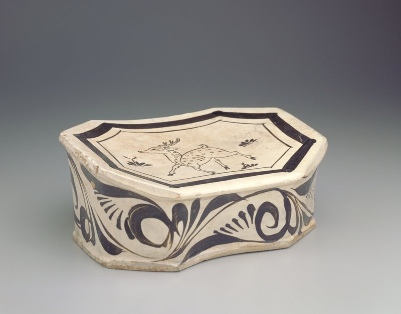 ceramic pillow with painted glaze decoration in black of deer profile and foliage on top; scroll designs on outer edges; white glaze