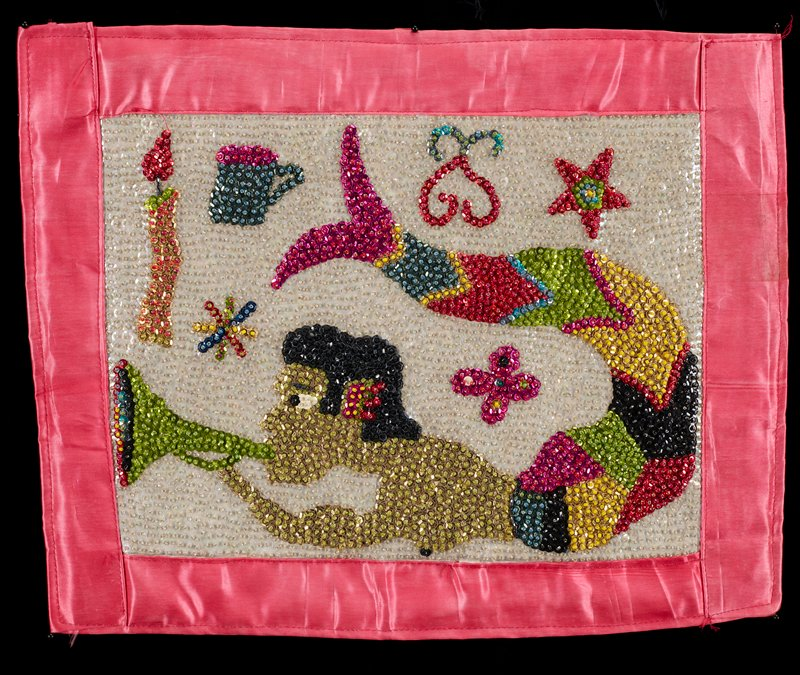 beaded and sequined panel with pink trim and backing; mermaid blowing a green horn with flower, stars, coffee cup, candle and scrolls on white ground