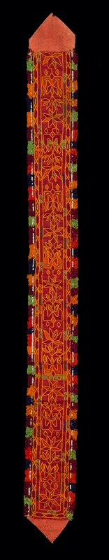 """red with red and yellow chain stitch floral embroidery; short, multicolored silk fringe on both long edges with white metal braid; each red lining ends with face-exposed, 2"""" chevrons; all hand stitched"""