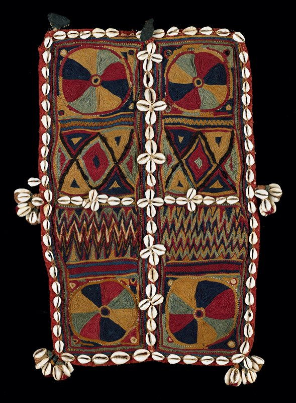 multi-colored wool chain stitch embroidery; two rows of four squares in pie shapes, diamonds and zig-zag designs; rows of shells divide the panels in half in both directions; clusters of shells at bottom corners and sides; row of shells surround; embroidery applied to tan, gauze-like cotton; edged in red cotton