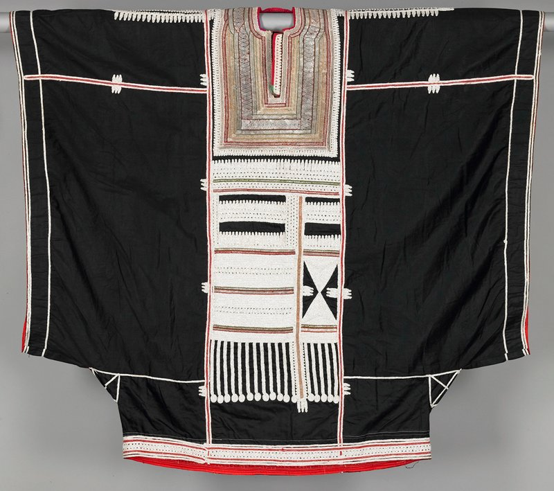 """black cotton wide dress with very wide (31"""") red faced sleeve openings; shoulders, lower edge, upper back, center and lower front have applied white, silver and red tape in elaborate patterns; around neck back and down bib front are rows of applied wide and narrow interwoven metal tapes edges in red, yellow and green; keyhole-type neckline"""