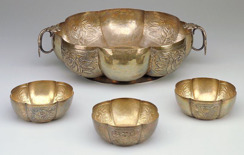Bowl with eight hammered lobes; alternating lobes have impressed floral design; two applied floral and leaf handles; applied hammered foot