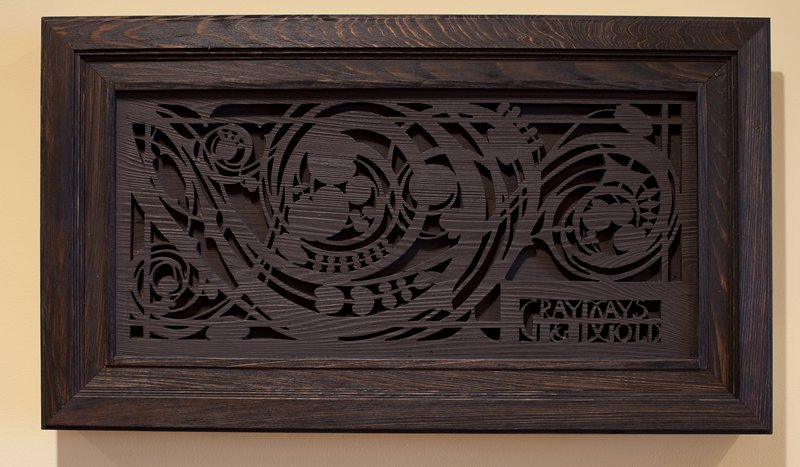 "Sullivan-style design cut out of top layer of wood with second layer below; ""GRAY DAYS/ & GOLD"" carved in LRC; dark brown"