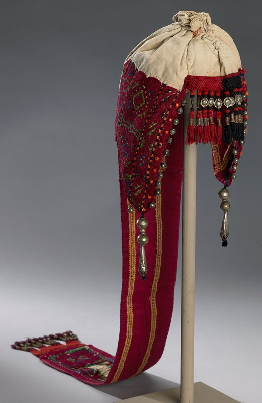 """red; natural muslin seamed and gathered at top to form cap; ear flaps and long strip down back; top front edged red and black; applied woven edging with knotted, wrapped fringe with oval metal and tassels; front sides edged in metal beads and red coral; flaps end with 1/2"""" round beads and one long teardrop bead; lined with red cotton fabric with yellow stripes; long back strip edged same as ear flaps; ear flaps and long black strip have heavy silk embroidery with chain stitch; red with some blue and green outlining also in chain stitch; floral patterns; hat has interlining of coarse weave, natural cotton; edged in trim that looks like chain stitch; red lining does not completely cover inside of cap exposing the coarse weave interlining; front of cap lined in multi-colored cotton twill; center of long back strip exposes muslin with rows of yellow stitching"""