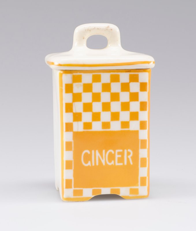 "small square container with cover with small handle; white porcelain decorated with yellow-orange checkerboard and ""GINGER"" in white on front; stripe around edge of cover on front and sides"