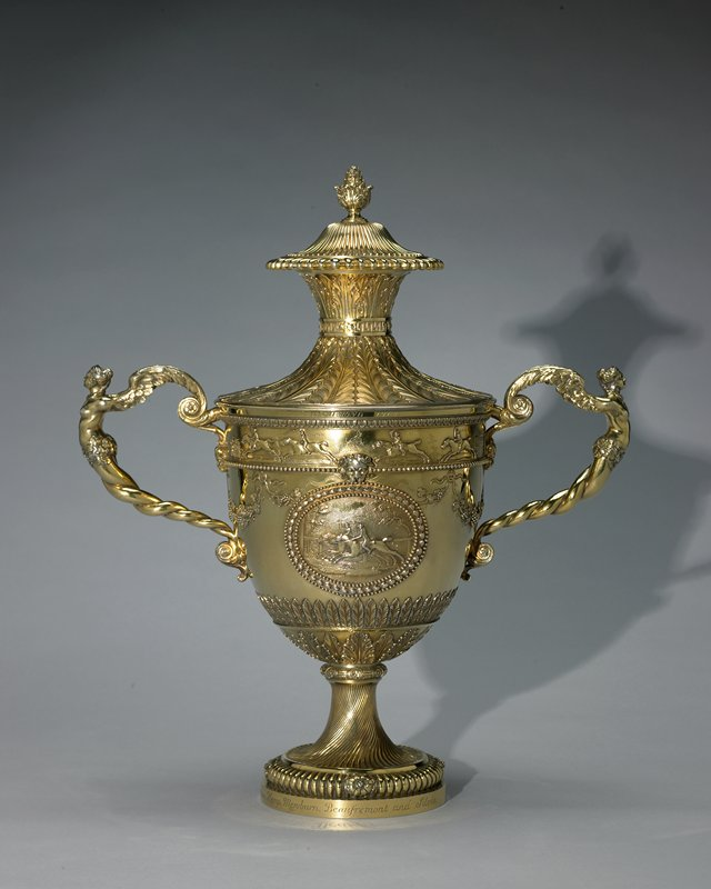 loving cup with cover; handles are maidens with wings in place of arms; cartouche of two horses and jockeys racing on one side, two horses with jockeys and grooms opposite side; racing horses, jockeys, spectators and grooms in frieze around top; gold patina