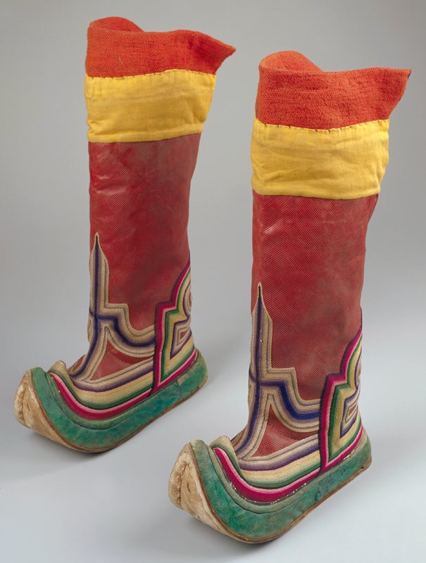 red leather with stamped hatching on leg, orange hatched leather on foot; green leather banding between foot and leg and around edge of sole; applied black leather appliques of scrolled designs; curled and pointed toe